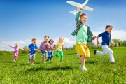 Active running kids with boy holding airplane toy