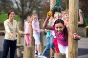 School children at break time playing on climbing frame